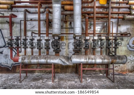 Old big and small pipes with valves and label - stock photo