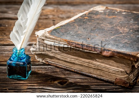 Old big book and pen with blue ink - stock photo