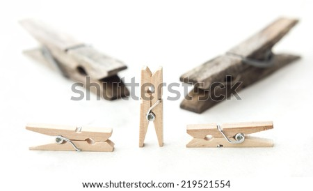 Old big clothespins against some more small and new ones isolated on a white textured background. - stock photo