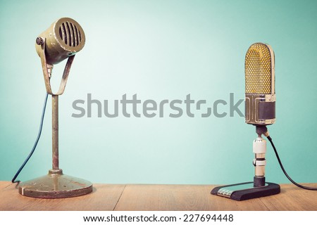 Old big retro studio microphones front mint green wall background - stock photo