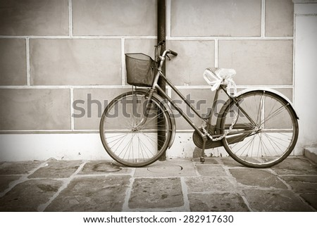 Old bike against the wall - toned image - stock photo