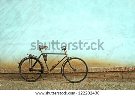 Old bike in front of the wall, colored,retro