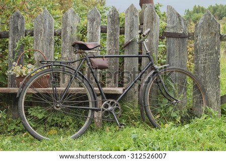 Old bike standing at the wooden fence. Still life of village life.