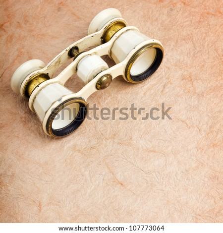 Old binoculars on vintage paper background