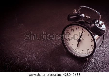 old black alarm clock with leather background