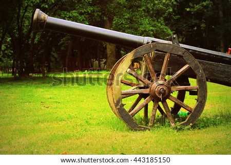 Old black cannon with wooden wheels on grass. Original historical iron