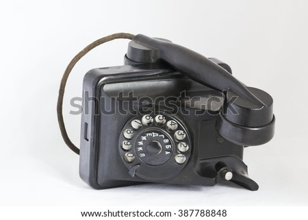 Old black dial phone on its side. - stock photo