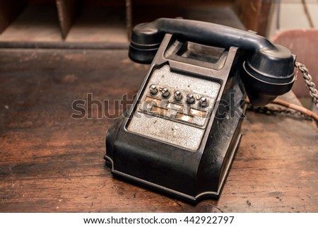 Old black dusty telephone with buttons on desk