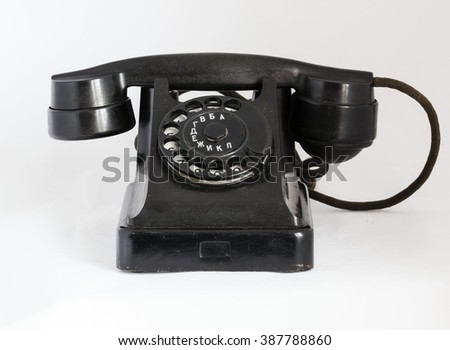 Old black ebonite telephone frontally. - stock photo