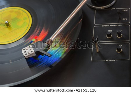 Old black gramophone during playing colorful vinyl plate lighting by colored light. Creative close up product macro photography by using long time exposition. - stock photo