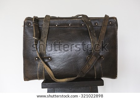 old black leather bag frontal view on white background - stock photo