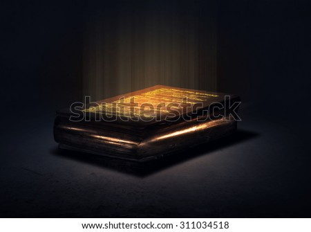 Old black magic book with lights on pages - stock photo