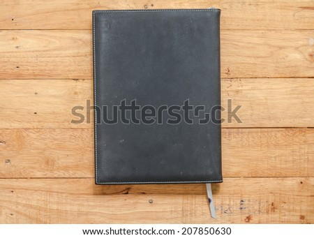 Old black notebook lay on a wooden table.