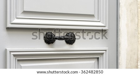 Old Black Painted Brass Door Handle on sturdy old grey wooden entrance door - stock photo