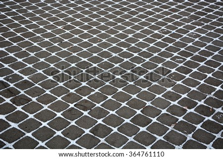 Old black pavement with snow as a background - stock photo