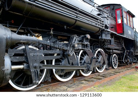 Old Black Steam Locomotive Train with closeup of wheels and boiler - stock photo