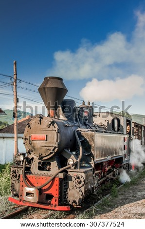 Old black steam powered railway train. Restored old vintage steam train built at Resita, Romania. - stock photo