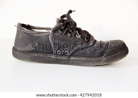 OLD BLACK STUDENT CANVAS SHOES ISOLATED ON WHITE BACKGROUND WITH CLIPPING PATH - stock photo