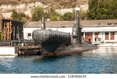 Old black submarine standing in docks - stock photo