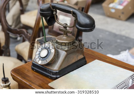old black telephone brass and copper on wood table / vintage telephone in a street market, photo lateral, natural light
