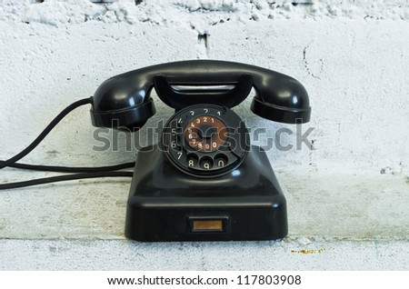 Old black telephone with rotary dial in white room - stock photo