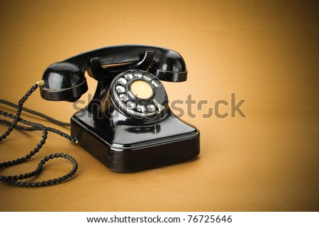 old black telephone with rotary disc on brown background - stock photo