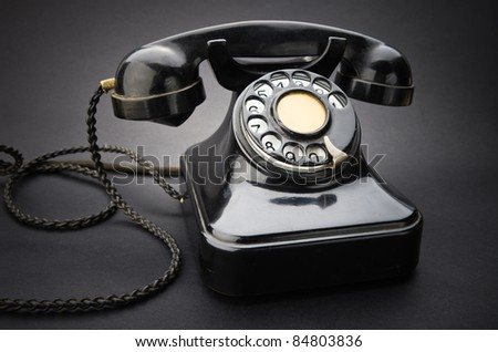 old black telephone with rotary disc on gray background - stock photo