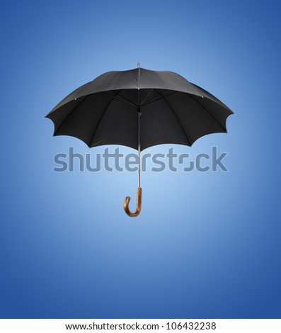 Old black vintage umbrella against blue background.