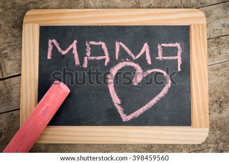 Old blackboard with Word Mama and a Heart, written with pink chalk, vintage wooden table - stock photo
