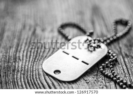 Old blank dog tag on wooden background. Very shallow depth of field with focus on the lower part of a tag - stock photo