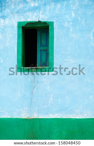 Old blue adobe wall with a window. Architecture background. - stock photo