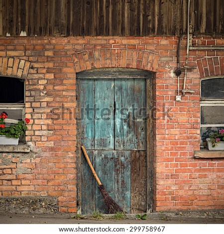 Old blue barn door with broom and windows