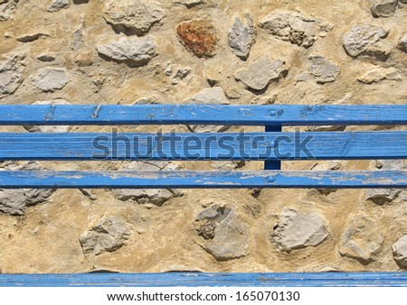Old blue bench, against rustic wall. - stock photo