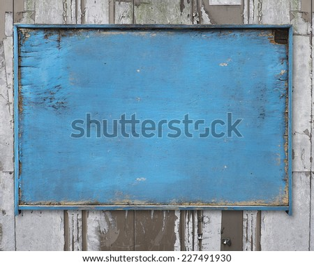 old blue blank weathered wood noticeboard on rough dirty wall background - stock photo