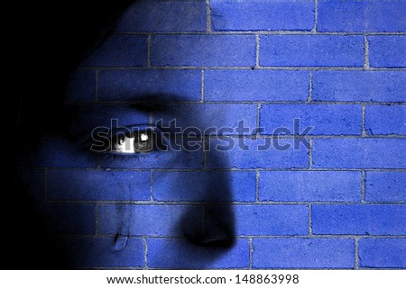 Old blue brick wall with face blending in - stock photo