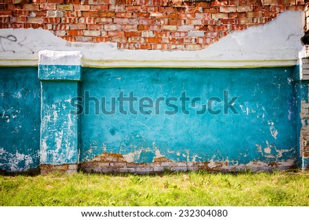 Old blue brick wall with green grass   - stock photo