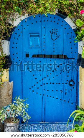 Old Blue door with arch from Sidi Bou Said and flowers - stock photo