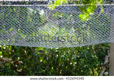 old blue fishing net with blurry forest background,select focus with shallow depth of field:ideal use for background - stock photo