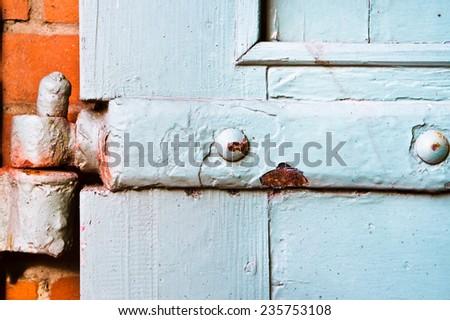 Old blue hinge on a wooden door - stock photo