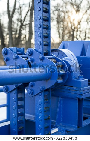 Old blue mechanism of flood gate - stock photo