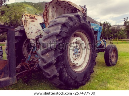 old blue rusty tractor outdoors in a farm  - stock photo