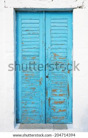 Old blue textured door with cracks - stock photo