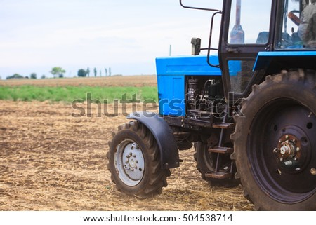Old blue tractor in a field on a bright sunny day