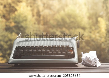 old blue typewriter and crumpled paper sheet, vintage stock potho - stock photo