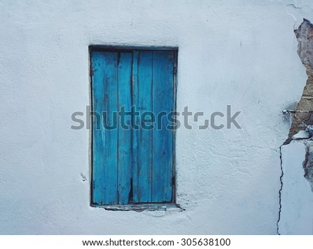 Old blue window on white wall - stock photo