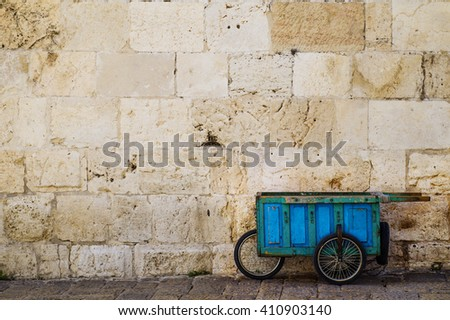 Old blue wooden cart. Wooden wheelbarrow standing near a stone wall. The old self-made wooden cart on three wheels with handles. - stock photo