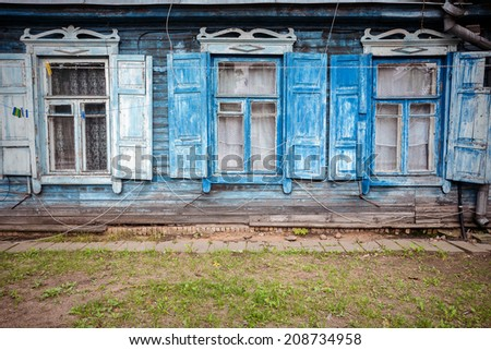 Old blue wooden wall with some windows - stock photo