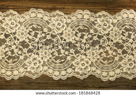 Old boards covered with beautiful lace - stock photo