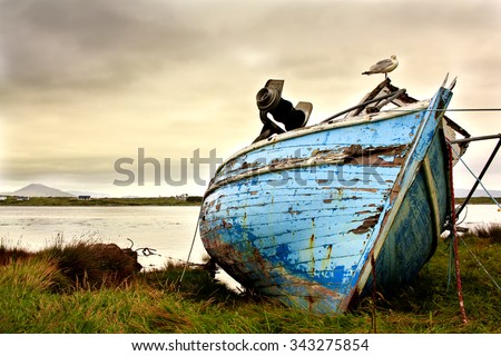 Old boat abandoned on the coastline in Ireland. Moody sky and run-down boat express lonliness and sadness.  - stock photo