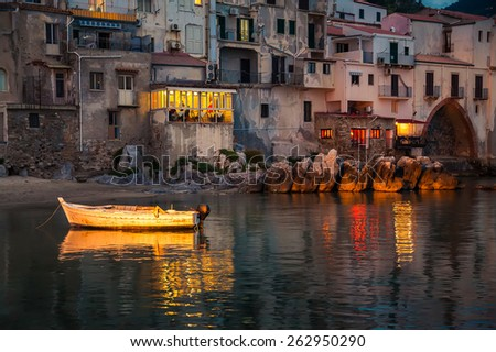 old boat drifting in a harbor of Cefalu at dusk, Sicily - stock photo